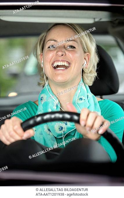 Laughing female car driver hears music