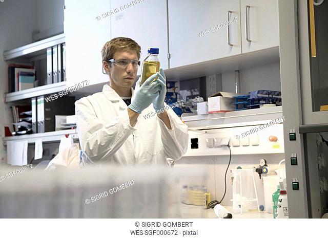Scientist in a biological lab analyzing liquid