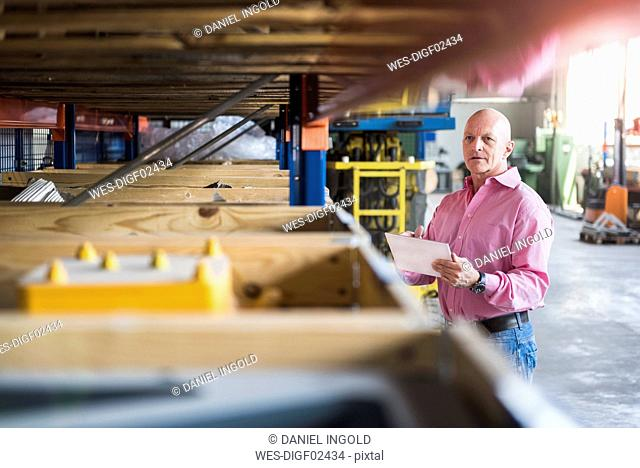 Man with tablet in industrial hall looking at shelves