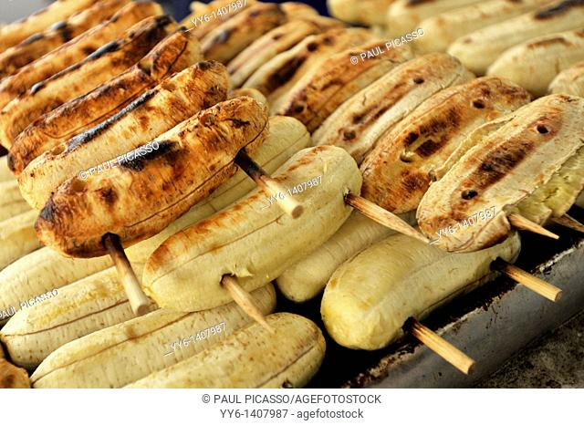 thai bbq bananas, Traditional Thai food cooked on an open charcoal stove, street market , Bangkok, thailand