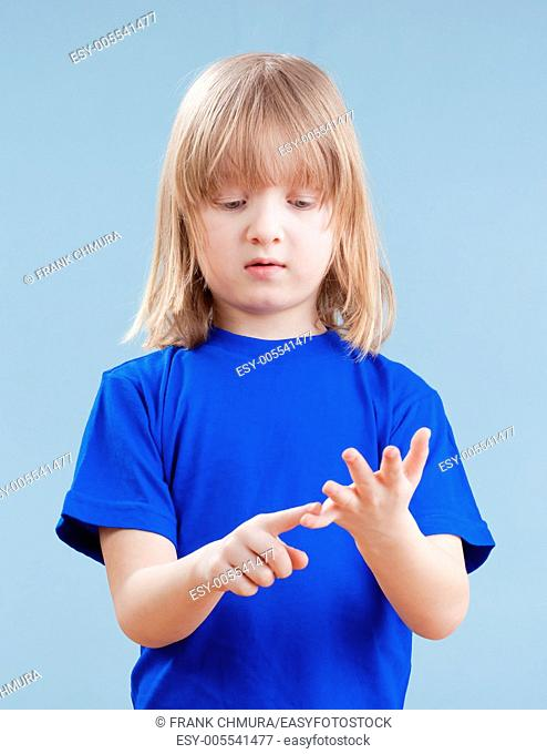 boy with long blond hair counting on fingers of his hand - isolated on blue