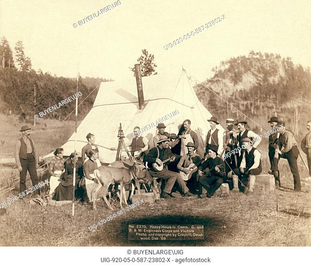 Small group of men and women and two deer in front of a tent. Some of the men are playing musical instruments