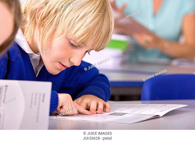 School boy reading workbook in classroom