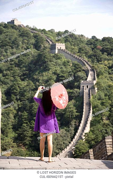 Rear view of mid adult female tourist photographing on the Great Wall of China, Beijing, China