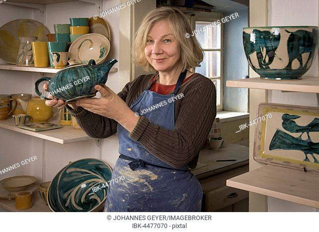 Ceramic workshop, woman holding finished teapot, shelves with pottery, Pittenhart, Upper Bavaria, Germany