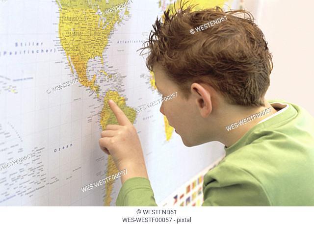 Boy (8-9) looking at world map, close-up