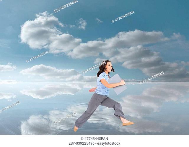 Composite image of cheerful businesswoman jumping while holding clipboard over a lake and cloudy sky