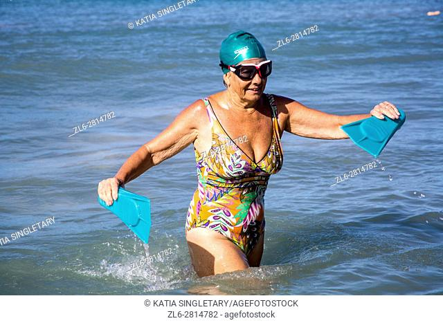 Senior retired caucasian woman, in her 70's, with her swim cap, flippers and goggles, going to the ocean doing her exercices to stay fit
