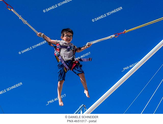 Five-year-old boy doing bungee trampoline