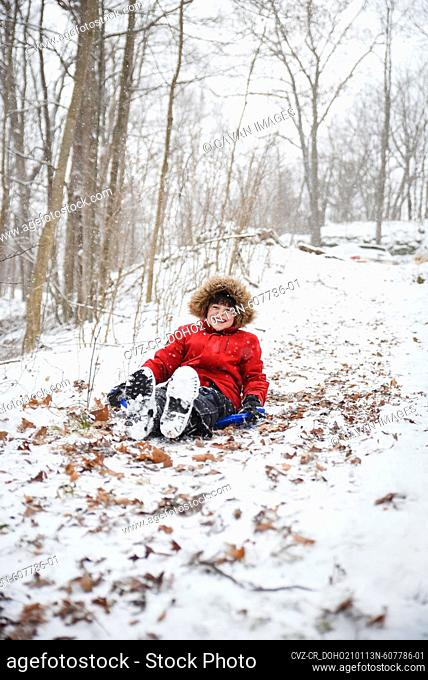 Happy boy sledding down a hill in the woods on a snowy winter day