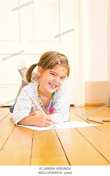 Portrait of laughing little girl lying on wooden floor with crayons and sheet of paper
