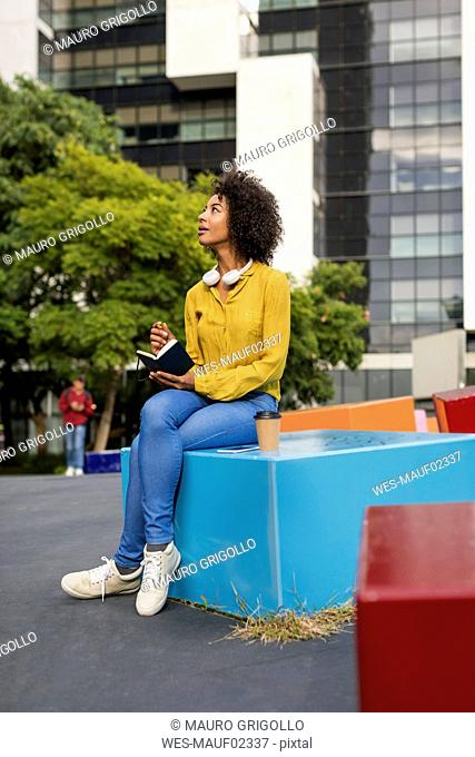 Woman sitting on bench with smartphone and coffee writing in notebook