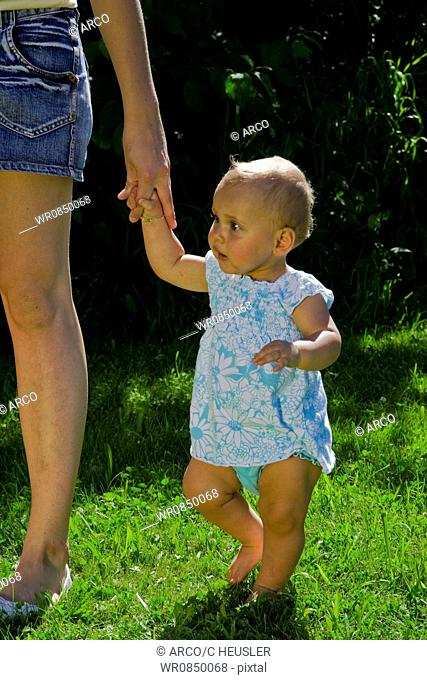 Baby at mother's hand, mother and daughter / lawn