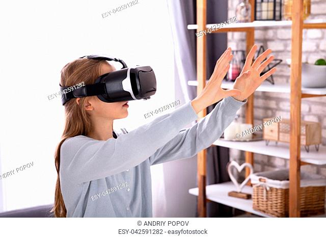 Side View Of A Girl Using Virtual Reality Headset At Home