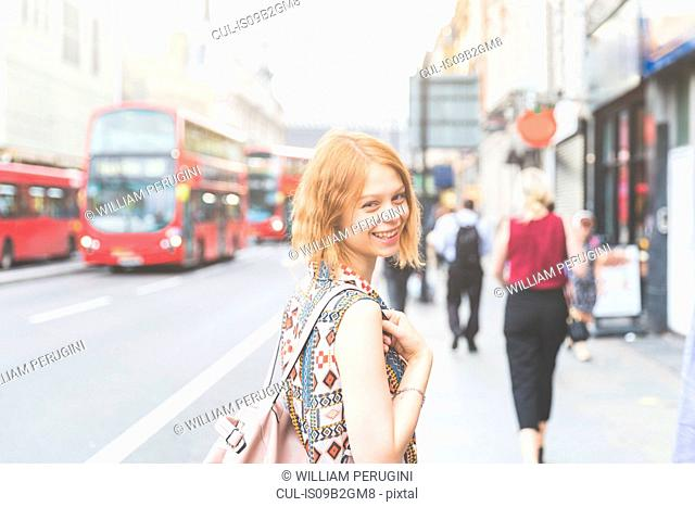 Woman in street looking over shoulder at camera smiling, London, UK