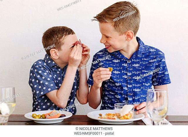 Two young boys eating tapas, laughing and making salami eyes