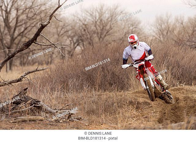 Motorcyclist riding dirt bike on rural path