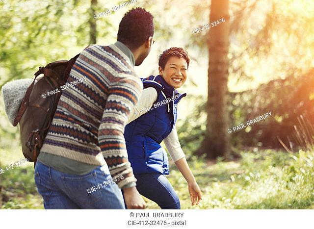 Laughing couple hiking with backpack in woods