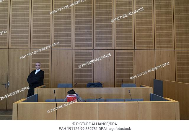 26 November 2019, Rhineland-Palatinate, Mainz: With a writing pad, the 28-year-old defendant covers his face in the dock in the courtroom of the regional court