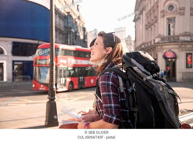Two women backpackers in city with map and guidebook