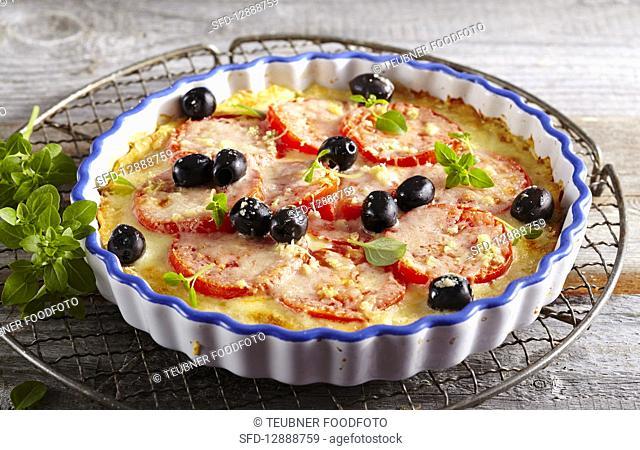 Potato pizza with tomatoes, mozzarella, oregano, basil and olives in baking dish