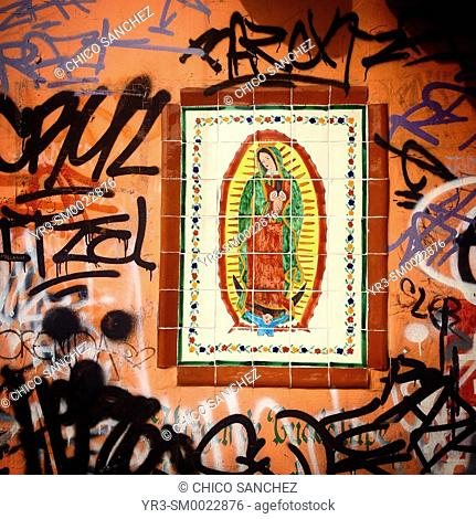 An image of Our Lady of Guadalupe surrounded by graffiti in Mexico City, Mexico
