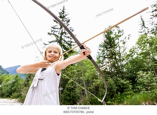 Smiling girl aiming with bow and arrow in the nature