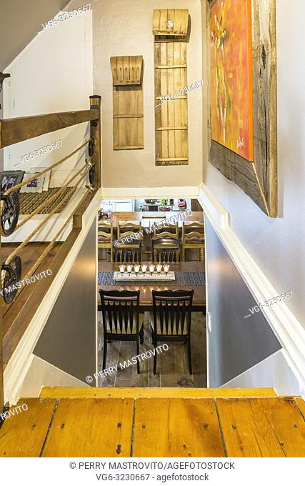 Looking down pinewood staircase decorated with framed painting and toboggans leading to dining room-kitchen area with lit candles on dining table inside an old...