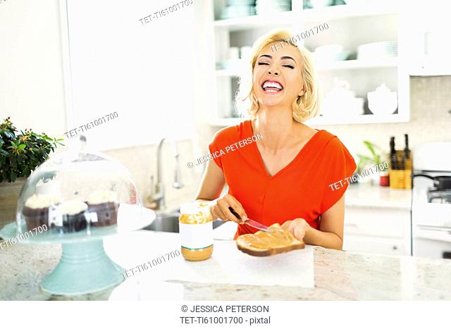Woman making toast with peanut butter in kitchen and laughing
