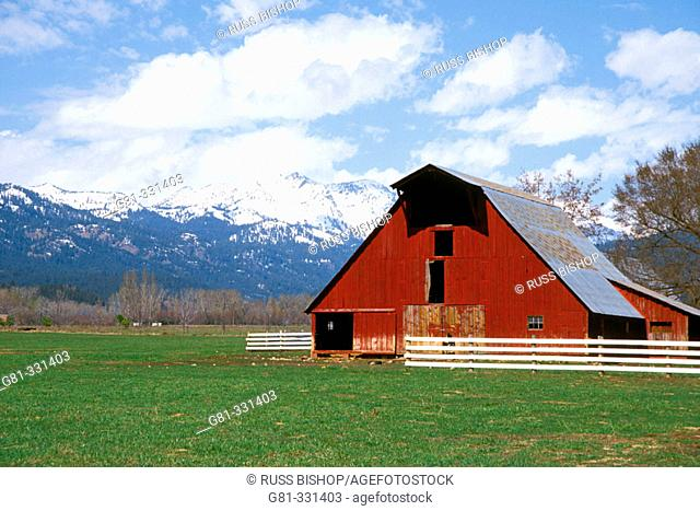 Red barn under the snow-covered Wallowa Mountains. Halfway. Oregon. USA