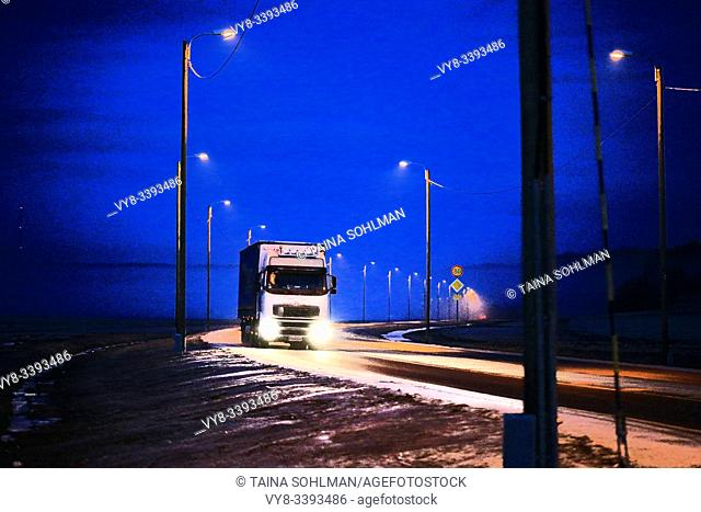 Lorry pulling semi trailer on the road at speed under deep blue sky on a winter evening