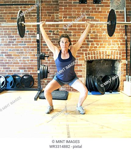 Caucasian woman lifting weights in gymnasium