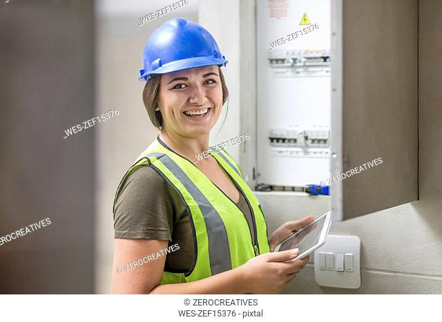 Portrait of smiling female electrician with tablet at fusebox
