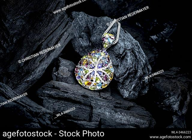 A coloured Diamond neckless on black coals as background