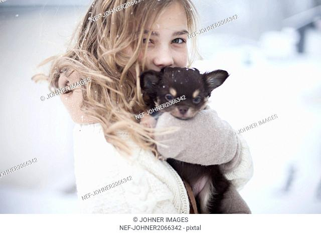 Young woman holding puppy in winter scenery