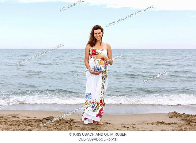 Pregnant woman standing on beach, hands on stomach