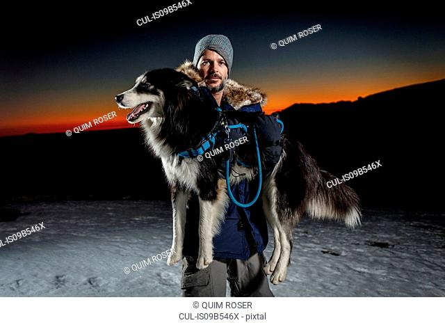 Portrait of mature man carrying dog in snow at night