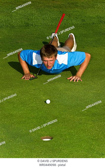 A golfer lining up a put on the green