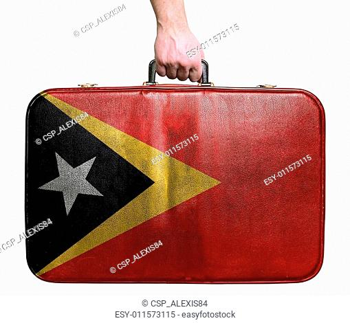 Tourist hand holding vintage leather travel bag with flag of East Timor