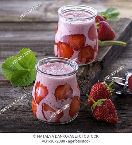 yogurt with fresh red strawberries in a glass jar on a gray wooden table, close up