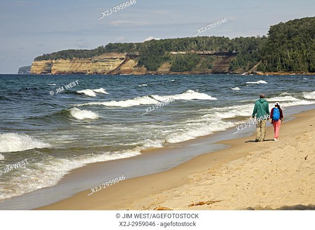 Munising, Michigan - Two people walk along the beach of Lake Superior in Pictured Rocks National Lakeshore