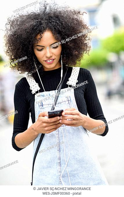 Young woman with earphones looking at cell phone