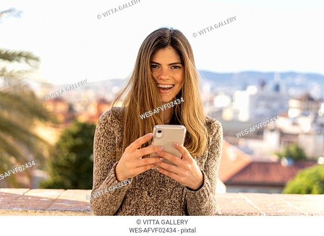 Portrait of laughing young woman holding cell phone