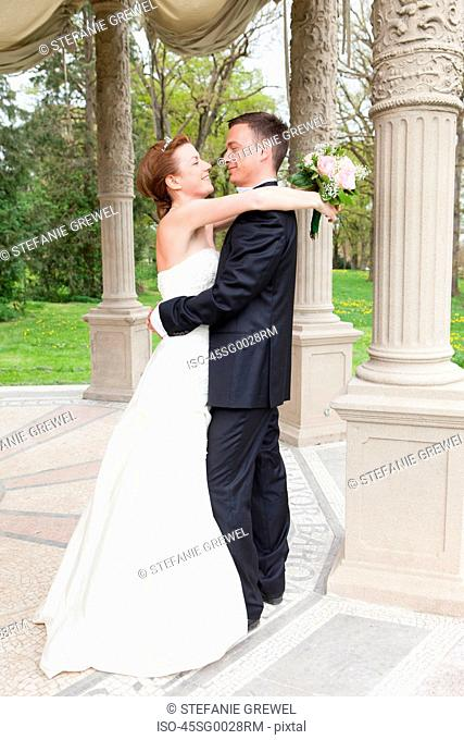 Newlywed couple hugging outdoors