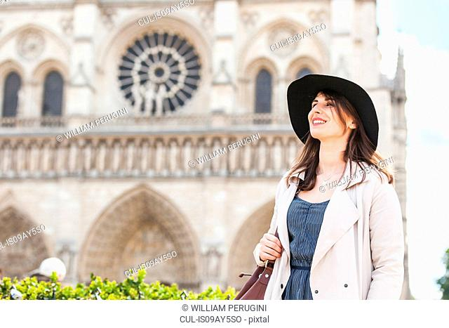 Stylish young woman at Notre Dame, Paris, France