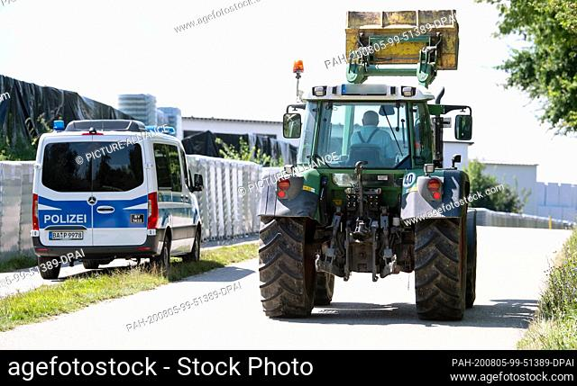 05 August 2020, Mamming: A farmer drives his tractor past a police car and a cannery. The number of corona infected people in Mamming continues to rise: 166 of...