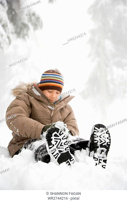 Boy sitting in the snow