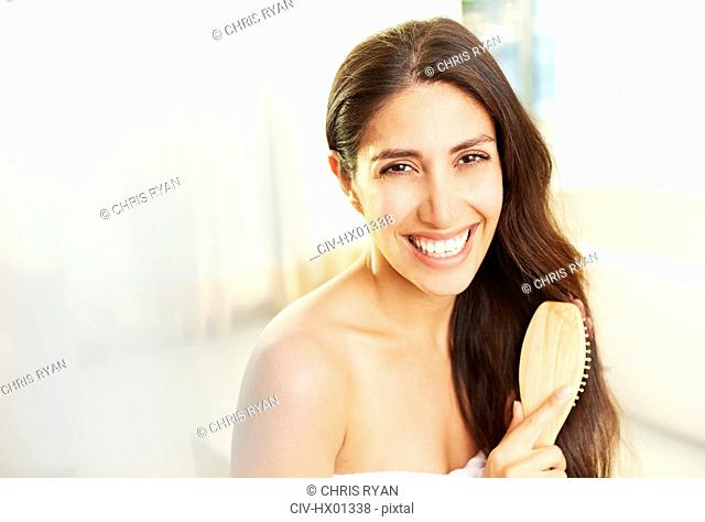 Portrait smiling brunette woman brushing hair