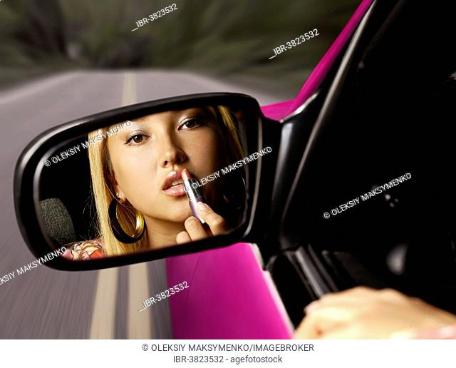 Young woman applying lipstick in a car on a highway, looking in a rear view mirror, distracted driving