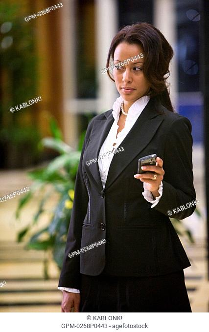 Businesswoman holding mobile phone outside office building